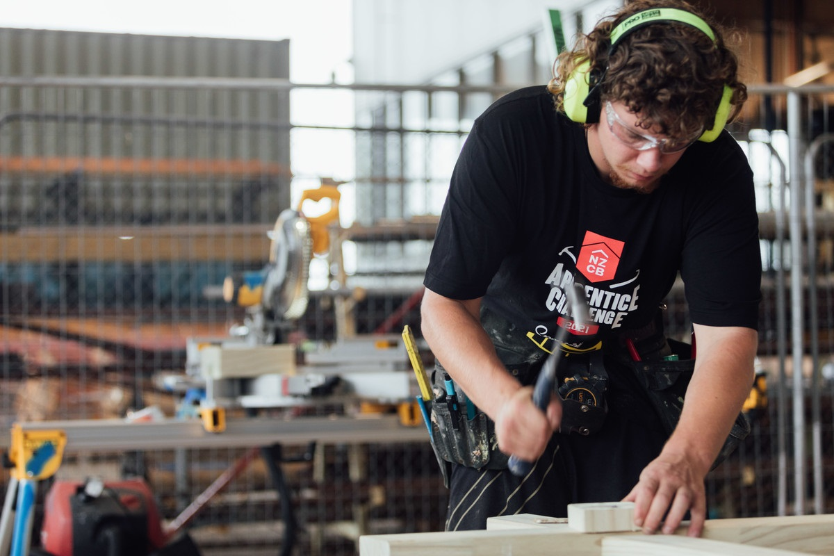 Unitec participant Harrison Forbes using a hammer to nail in a piece of wood at the NZCB apprentice challenge