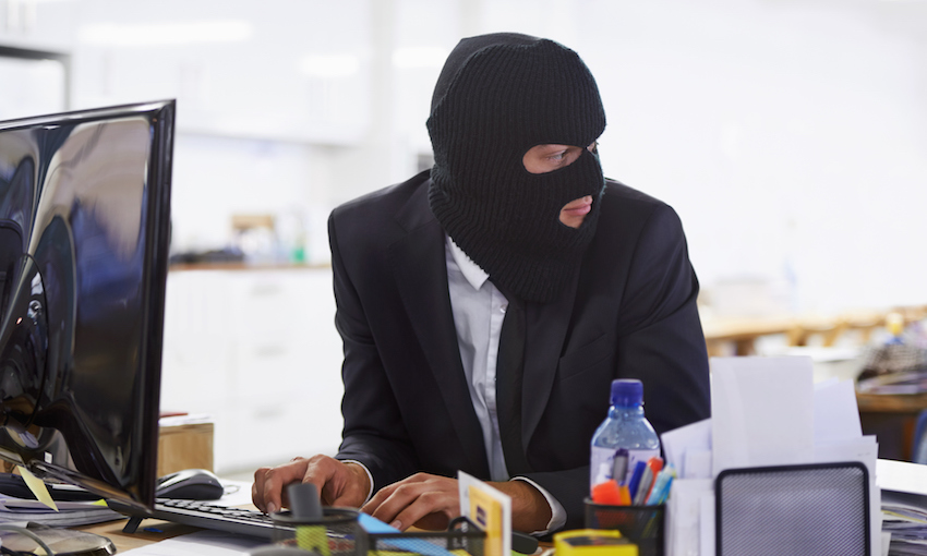 Shot of a hacker dressed in a black mask hacking a computer coming to steal your data. (image: getty images)