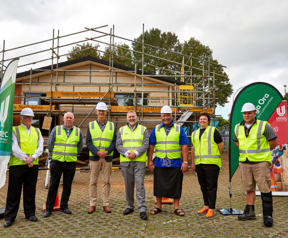 Unitec and Kāinga Ora staff standing in front of a half-built house with hard hats and PPE gear, smiling